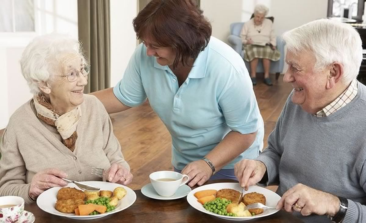 nurse giving residents their food